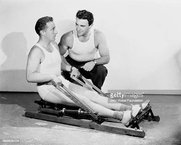 Actor Bing Crosby being tutored while using an exercise machine for Paramount Pictures 1934