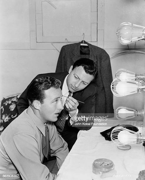 Actor Bing Crosby getting his makeup applied by a friend in front of a mirror for Paramount Pictures 1936