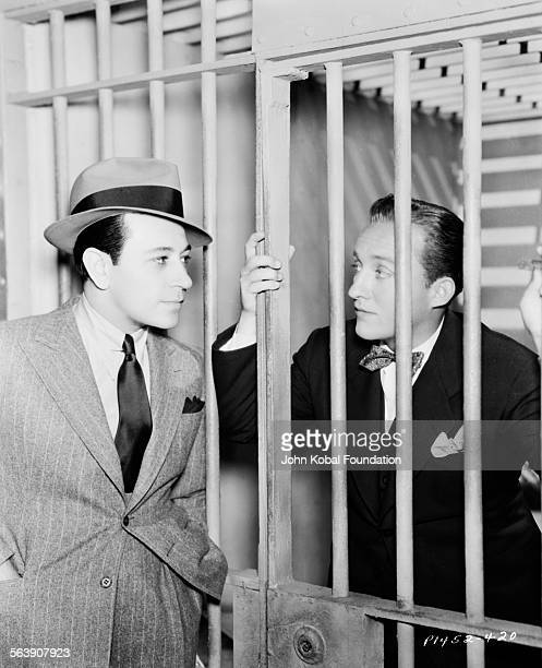 Actor Bing Crosby is behind bars with George Raft on the left in a scene from a film, for Paramount Pictures, 1935.