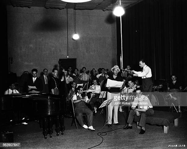 Actor Bing Crosby singing with a band in a large studio for Paramount Pictures 1934