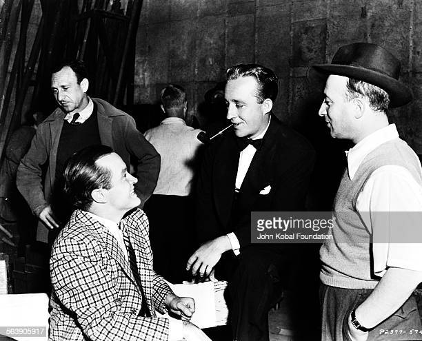 Actor Bing Crosby smoking a pipe and talking to Bob Hope with director David Butler on the set of the film 'Road to Morocco' for Paramount Pictures...