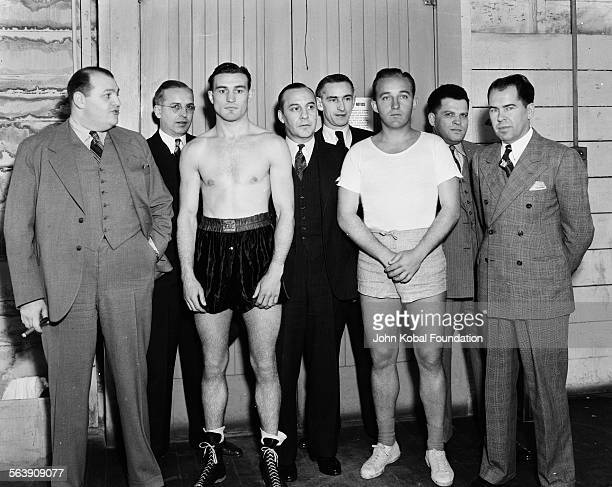 Actor Bing Crosby wearing shorts and a tshirt with an unknown boxer and a group of men in suits for Paramount Pictures 1935