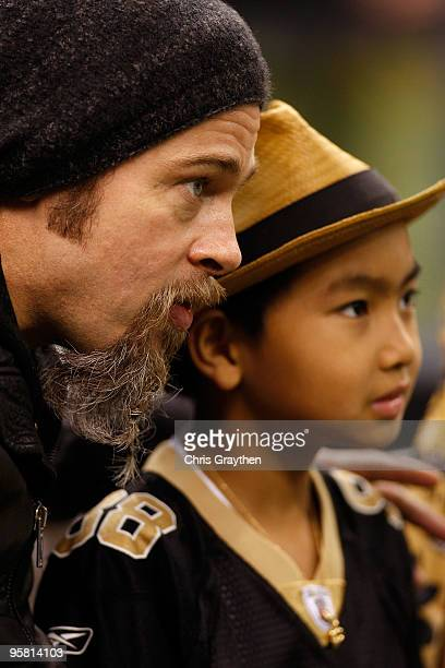 Actor Brad Pitt and his son Maddox Jolie-Pitt sit on the bench on the sidelines during warm ups prior to the New Orleans Saints hosting the Arizona...