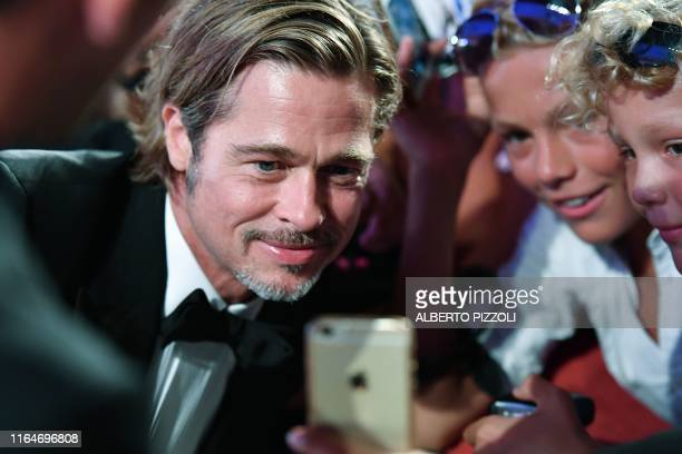 US actor Brad Pitt poses for selfie photos as he arrives on August 29 2019 for the screening of the film Ad Astra during the 76th Venice Film...