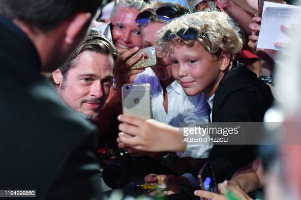 TOPSHOT US actor Brad Pitt poses for selfie photos as he arrives on August 29 2019 for the screening of the film Ad Astra during the 76th Venice Film...