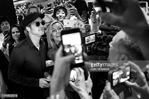 US actor Brad Pitt poses for selfies as he arrives to attend a press conference for the film Once Upon a Time in Hollywood at the 72nd edition of the...