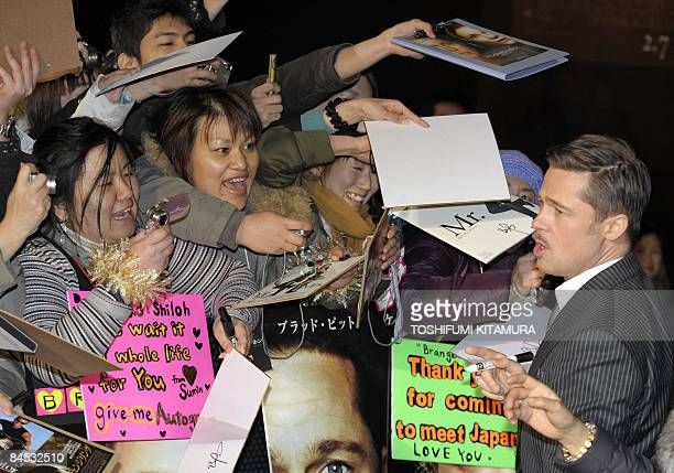 US actor Brad Pitt reacts to his fans as they request an autograph upon his arrival to attend the red carpet Japanese premier of his latest movie The...