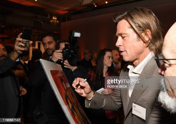 US actor Brad Pitt signs a poster during the 2020 Oscars Nominees Luncheon at the Dolby theatre in Hollywood on January 27 2020