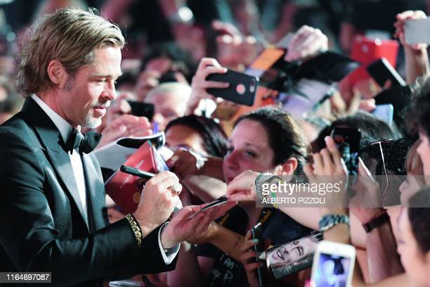 US actor Brad Pitt signs autographs for fans as he arrives on August 29 2019 for the screening of the film Ad Astra during the 76th Venice Film...