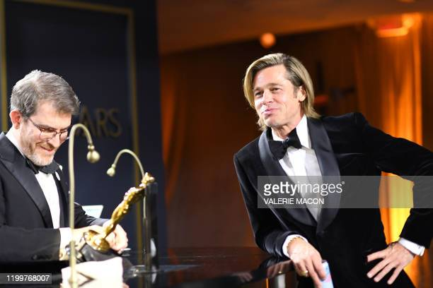 US actor Brad Pitt waits for his award for Best Actor in a Supporting Role to be engraved as he attends the 92nd Oscars Governors Ball at the...