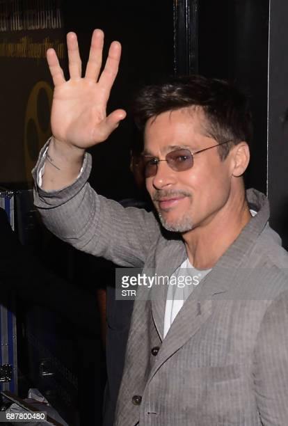 US actor Brad Pitt waves after attending the premiere of his latest movie War Machine in Mumbai on May 24 2017 The film will be released on Netflix...