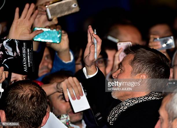 US actor Brad Pitt waves to his fans as they arrive to attend the Spain premiere of the film 'Allied' in Callao City Lights central Madrid on...