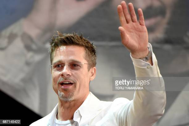 US actor Brad Pitt waves to his fans during the Japan premiere of his latest movie War Machine in Tokyo on May 23 2017 The film will be released by...