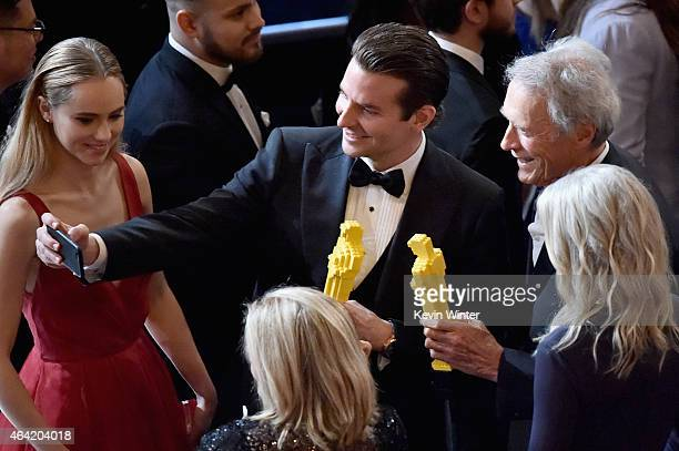 Actor Bradley Cooper and actor/director Clint Eastwood with guests take a selfie onstage during the 87th Annual Academy Awards at Dolby Theatre on...