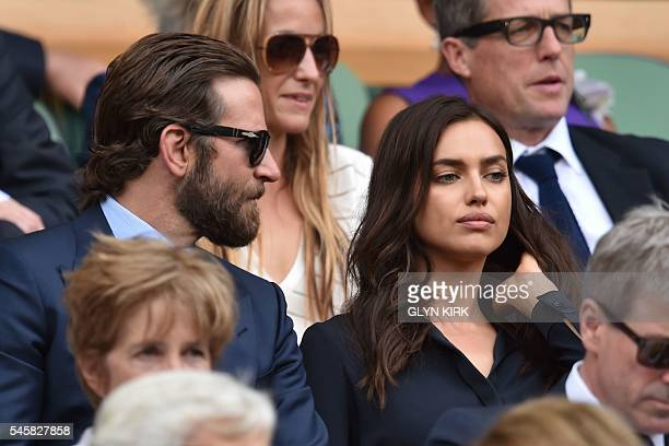 US actor Bradley Cooper and Russian model Irina Shayk sit in the royal box on centre court before the start of the men's singles final match on the...