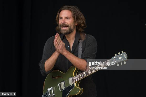 US actor Bradley Cooper plays a guitar as he is filmed for a remake of the film 'A Star Is Born' on the Pyramid Stage at the Glastonbury Festival of...