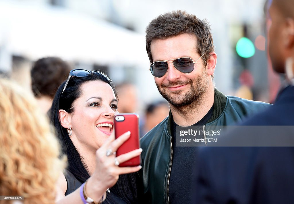 Actor Bradley Cooper (R) takes a seflie with a fan at the premiere of Marvel's 'Guardians Of The Galaxy' at the Dolby Theatre on July 21, 2014 in Hollywood, California.