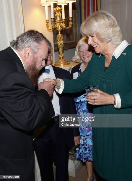 Actor Brian Blessed kisses the hand of Camilla Duchess of Cornwall as they attend a reception to celebrate the launch of the 'Our Amazing People'...