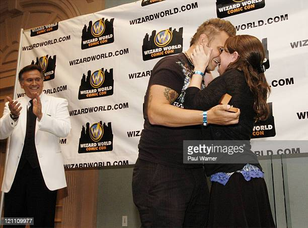 Actor Bruce Campbell claps as Jeremie Bailey hugs his fiancee AJ Zettler after she accecpted his marriage proposal at the Bruce Campbell question and...