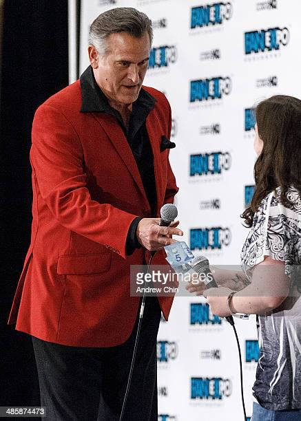 Actor Bruce Campbell gives five dollars to a panel participant at the Celebrity QA during Fan Expo Vancouver 2014 at the Vancouver Convention Centre...