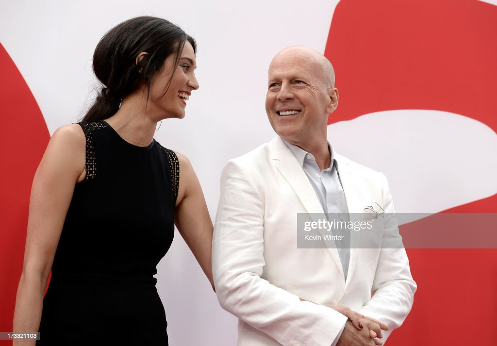 Actor Bruce Willis (R) and Emma Heming attend the premiere of Summit Entertainment's 'RED 2' at Westwood Village on July 11, 2013 in Los Angeles, California.