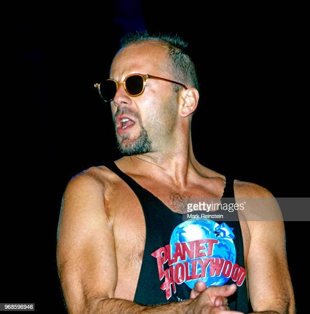 Actor Bruce Willis performing on stage at the grand opening of the Planet Hollywood night club Washington, DC, October 3, 1993.