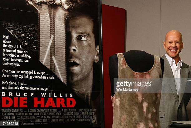 Actor Bruce Willis poses with objects from the Die Hard series of films that he donates to the Smithsonian's National Museum of American History June...