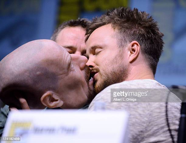 Actor Bryan Cranston watches actor Aaron Paul kiss a Walter White face mask onstage at the Breaking Bad panel during ComicCon International 2013 at...