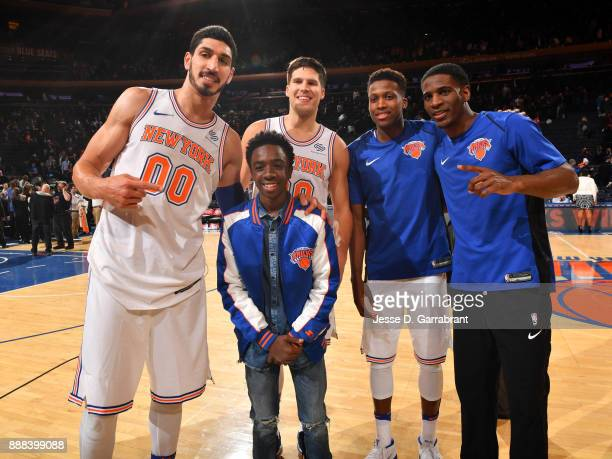 Actor Caleb McLaughlin poses for a photo with Enes Kanter Doug McDermott Frank Ntilikina Damyean Dotson of the New York Knicks before the game...