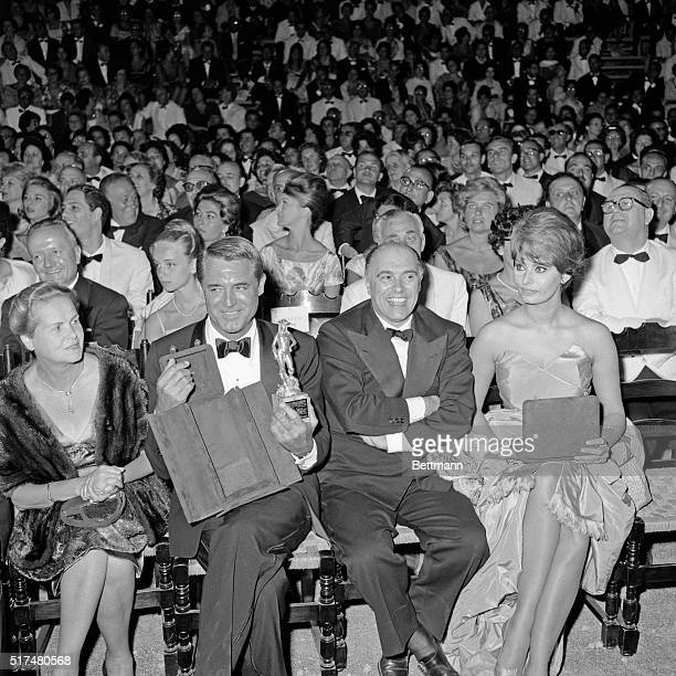 Actor Cary Grant shows off the 'Donatello David' trophy after receiving it July 30th Seated with Grant are actress Sophia Loren and her husband Carlo...