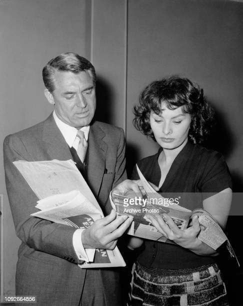 Actor Cary Grant shows Sophia Loren, his co-star in the movie 'The Pride and The Passion', a magazine sent to his hotel in Spain during filming,...