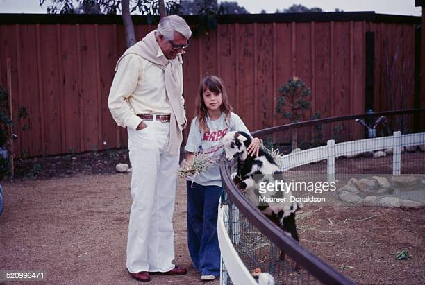 Actor Cary Grant with his daughter Jennifer and a goat 1975