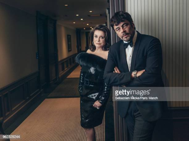 Actor Catherine Deneuve wearing an Yves Saint Laurent dress and Pomella jewellery is photographed with actor Benicio Del Toro during the 71st Cannes...