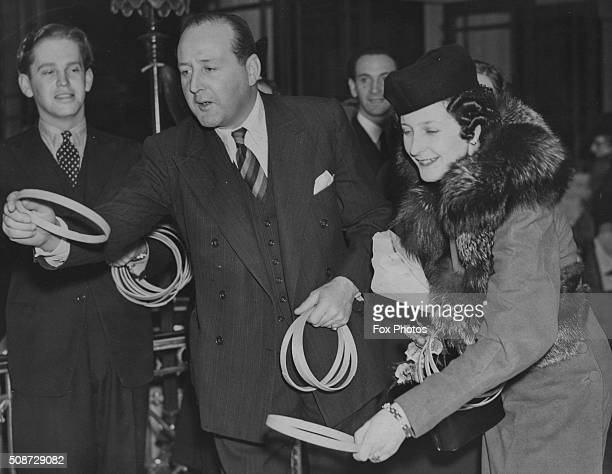 Actor Cecil Parker and Lady O'Neill playing a game of hoopla as they attend an annual Christmas fair at the May Fair Hotel London December 6th 1939