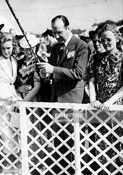 Actor Cecil Parker fishing for bottles of champagne at the Theatrical Garden Party Ranelagh England June 7th 1939