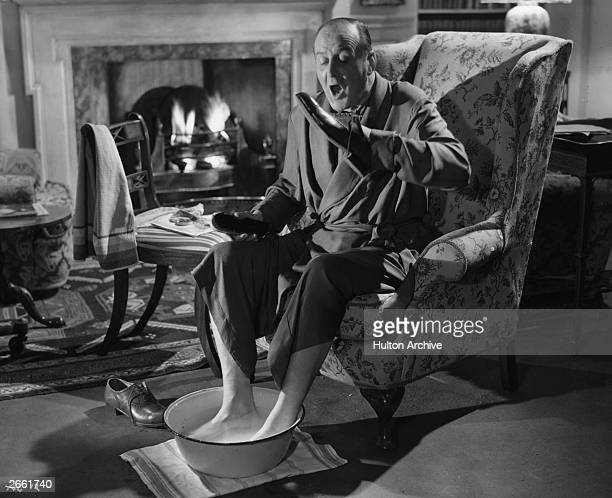 Actor Cecil Parker rests his feet in a bowl of water while he polishes his shoes in the film 'I Believe In You' directed by Basil Dearden for Ealing...