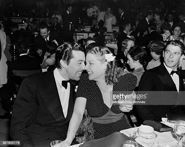 Actor Cesar Romero hugs actress Ann Sheridan at an event as actor Ronald Reagan looks on in Los Angeles California
