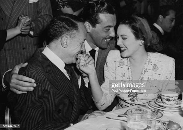 Actor Cesar Romero pictured with his arms around cinematographer Peverell Marley and his actress wife Linda Darnell at 20th Century Fox's studio...