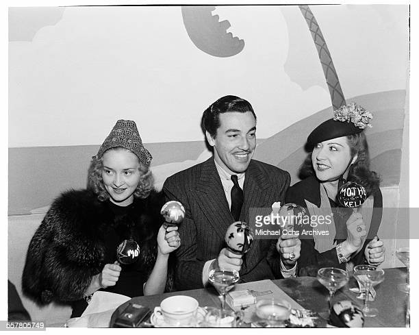 Actor Cesar Romero plays the maracas with actresses Virginia Bruce and Ethel Merman during an event in Los Angeles California
