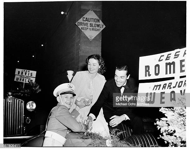 Actor Cesar Romero with actress Marjorie Weaver ride in the Hollywood Christmas Parade as they greet a boy in Los Angeles California