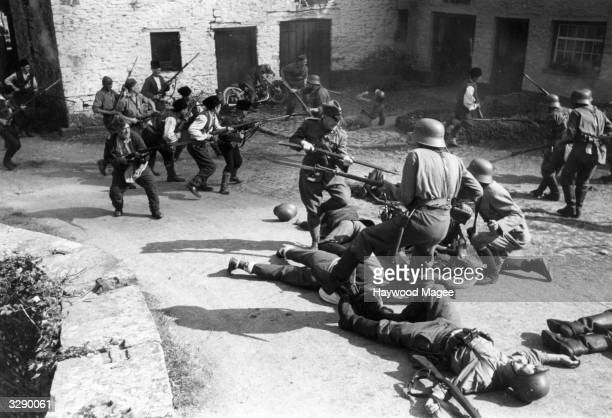 Actor Charles Victor leads the Yugoslav freedom fighters' attack on the occupying Nazi troops in a scene from the World War II film 'Undercover'...