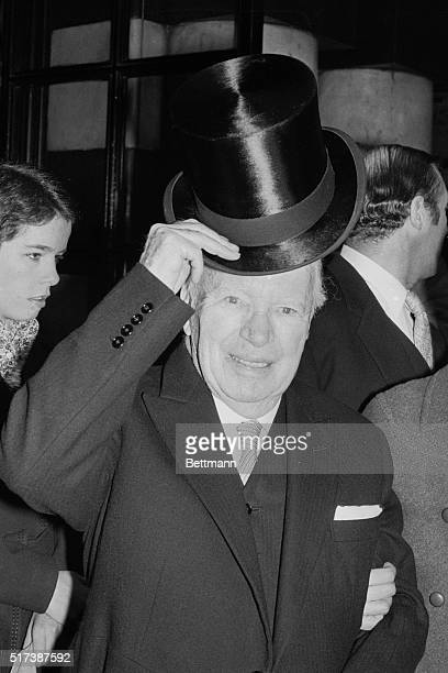 Actor Charlie Chaplin shown raising his hat to the press as he leaves a London hotel on the way to Buckingham Palace to be knighted by Queen...