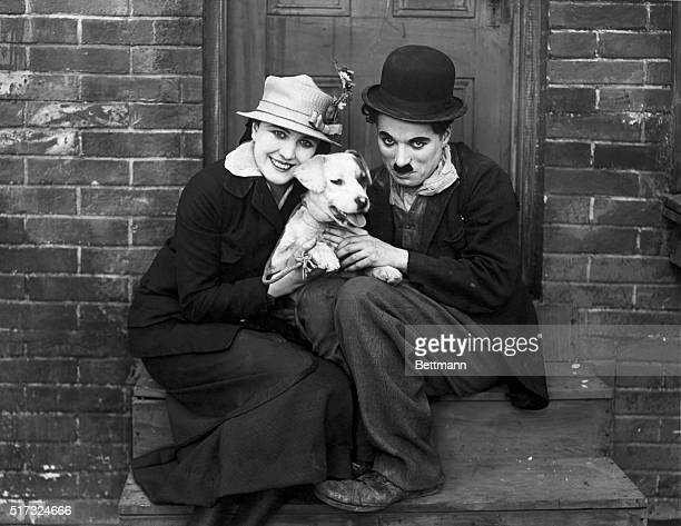 Actor Charlie Chaplin wearing his famous costume sits with actress Edna Purviance and a dog
