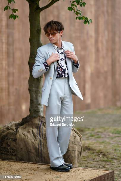 """Actor Charlie Heaton who portrays the character """"Jonathan Byers"""" in the Netflix series """"Stranger Things"""", wears sunglasses, a gray blazer jacket, a..."""