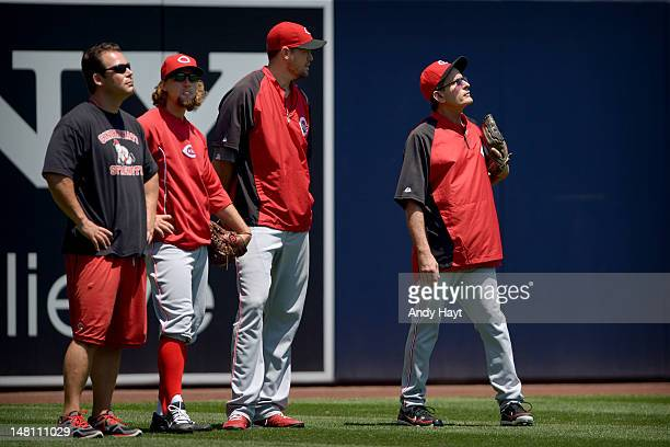 Actor Charlie Sheen shags balls in the outfield with Paul Lessard, trainer, Mike Leake, and Sean Marshall of the Cincinnati Reds prior to the game...