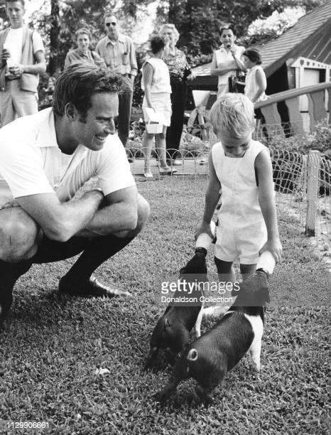 Actor Charlton Heston and his son Fraser Clarke Heston feed 2 pigs in circa 1959