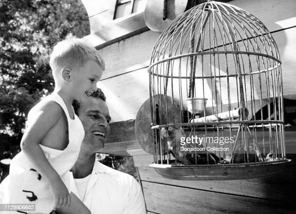 Actor Charlton Heston and his son Fraser Clarke Heston look at a bird in circa 1959