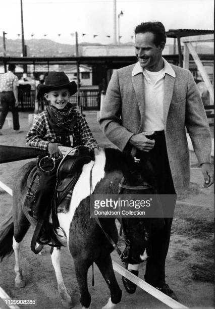 Actor Charlton Heston and his son Fraser Clarke Heston ride a minihorse in circa 1959