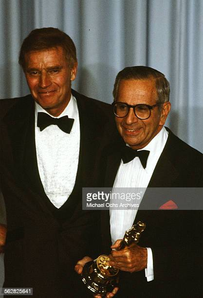 Actor Charlton Heston pose backstage with Walter Mirisch who receives the Jean Hersholt Humanitarian Award during the 55th Academy Awards at Dorothy...