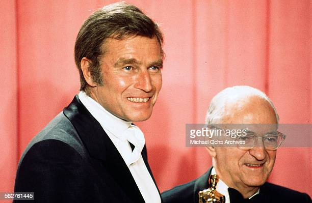 Actor Charlton Heston poses backstage with Dr Jules C Stein winner of the Jean Hersholt Humanitarian Award during the 48th Academy Awards at Dorothy...